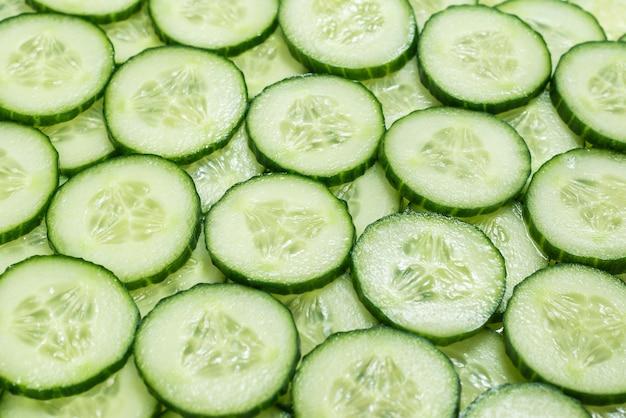 Verse groene plakjes komkommer als achtergrond