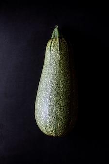 Verse groene pompoen pompoen courgette op zwart