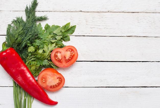 Verse groene salade, verse rode tomaten en rode peper op de witte rustieke tafel.