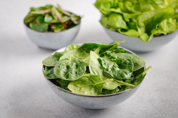 Verse groene saladebladeren in kommen