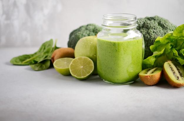 Verse groene smoothie in een kruik met ingrediënten op een grijze concrete achtergrond, selectieve nadruk.