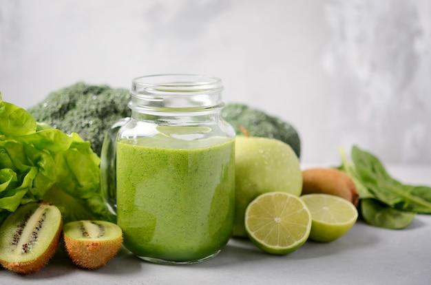 Verse groene smoothie in een pot met ingrediënten