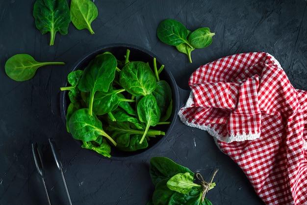 Verse groene spinazie in een ronde gietijzeren koekenpan