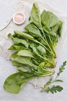 Verse groene spinaziebladeren en rucola met roze zout op een grijze achtergrond. bovenaanzicht