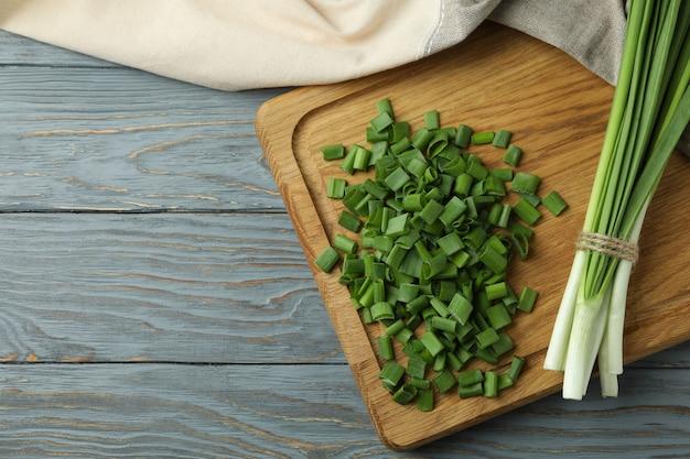 Verse groene ui op snijplank, op grijze houten tafel