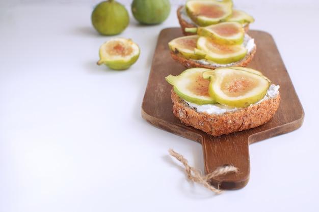 Verse groene vijgen broodjes canapeetjes houten snijplank volkorenbrood