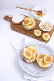 Verse groene vijgen houten snijbord porseleinen bord volkorenbrood honing