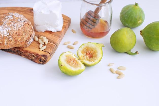 Verse groene vijgen houten snijplank volkorenbrood honing geitenkaas pijnboompitten