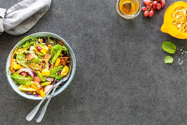 Verse groente- en fruitsalade in een plaat op zwarte steen. bovenaanzicht