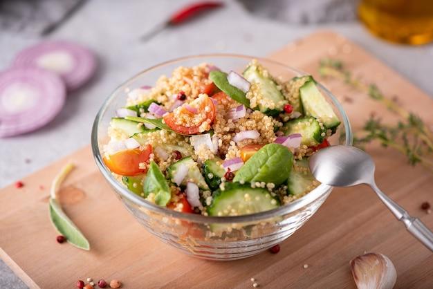 Verse groente en quinoa salade in een glazen kom op tafel, close-up
