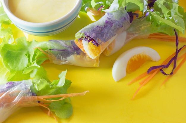 Verse groente salade roll met gekookt ei in noodle buis en slasaus op gele snijplank. verse groente salade roll met gekookt ei in noodle buis en slasaus op gele achtergrond