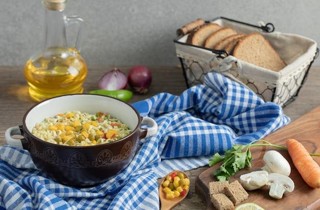 Verse groenten, brood, olie en noedels op houten tafel