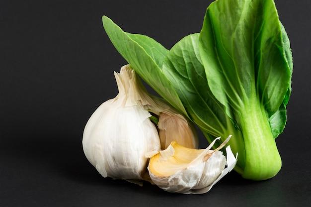 Verse groenten: choy bok of chinese kool en knoflook op zwarte achtergrond. gezond eten.