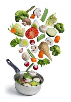 Verse groenten die in een pot vliegen, die op wit wordt geïsoleerd