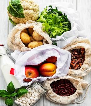 Verse groenten en fruit in eco katoenen tassen op tafel in de keuken. melk, aardappelen, abrikozen, rucola, bonen van de markt. zero waste shopping concept.
