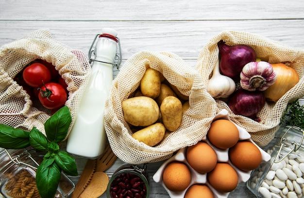 Verse groenten en fruit in eco katoenen tassen op tafel in de keuken.