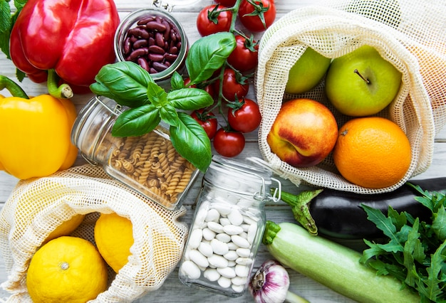 Verse groenten en fruit in eco katoenen tassen op tafel in de keuken