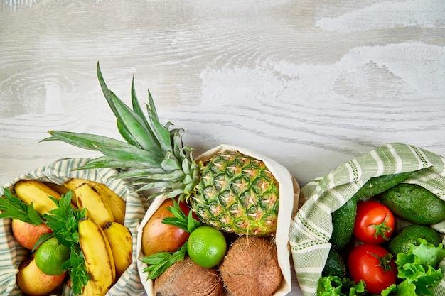 Verse groenten en fruit in eco katoenen zakken op tafel in de keuken.