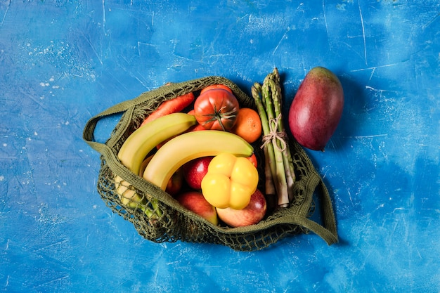 Verse groenten en fruit in een groene string tas. geen plastic, alleen natuurlijke materialen en natuurlijke producten.