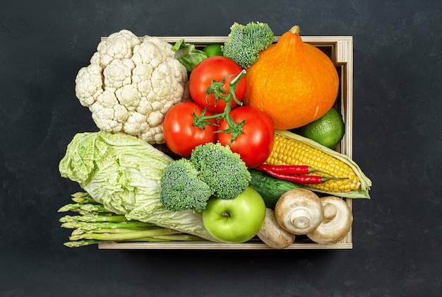 Verse groenten en fruit in een houten kist op een zwarte betonnen ondergrond, bovenaanzicht