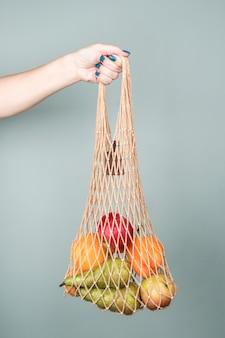Verse groenten en fruit in een string zak. milieuvriendelijke consumptie, afvalvrij productieconcept, vegetarisme.
