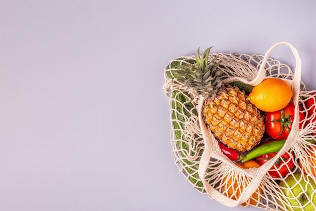 Verse groenten en fruit in zakgaas, bovenaanzicht.