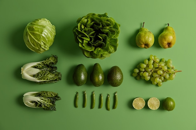 Verse groenten en fruit op heldergroene achtergrond. rijpe peren, druiven, limoen, kool, slasalade, erwten en paksoi voor gezond eten. creatieve lay-out. kruidenier en biologische producten.
