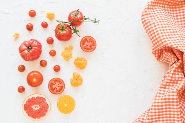 Verse groenten en geruit patroonservet op witte achtergrond