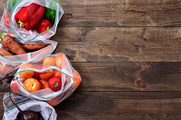 Verse groenten en greens in herbruikbare milieuvriendelijke zakjes op houten bruine achtergrond met kopie ruimte