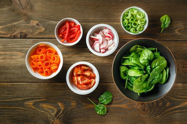 Verse groenten en greens op het houten aanrecht van de keuken, bovenaanzicht. ingrediënten voor salade - spinazie, wortelen, komkommers, tomaten en radijs. gezond eten concept