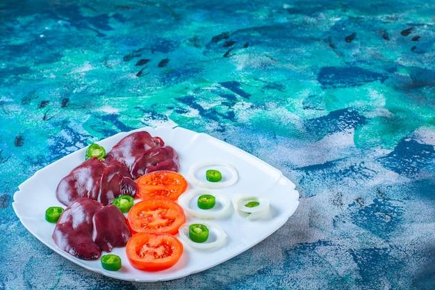 Verse groenten en kippenlevertjes op een bord