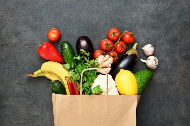 Verse groenten, fruit en greens in ambachtelijke papieren boodschappentas op zwarte rustieke achtergrond. eco winkelen en eten levering concept.