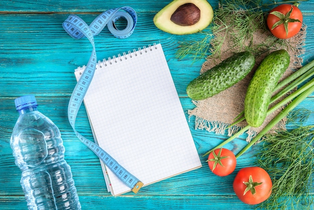 Verse groenten, houten plank en mes op blauwe achtergrond. tomaten, komkommers, avocado, dille en groene ui. ruimte voor tekst.