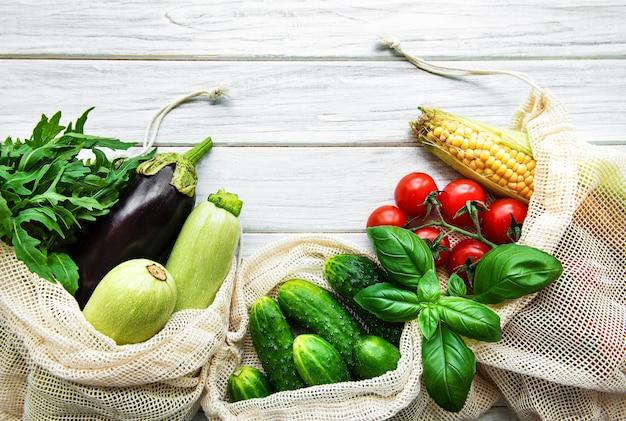 Verse groenten in eco katoenen zakken op tafel in de keuken