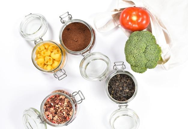 Verse groenten in een eco vriendelijke beige draagtas op witte muur. glazen potten met groene thee, muesli, koffie, pasta. zero waste concept, ronduit.