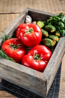 Verse groenten in een houten kist, rode tomaten, groene komkommers met kruiden. houten achtergrond. bovenaanzicht.