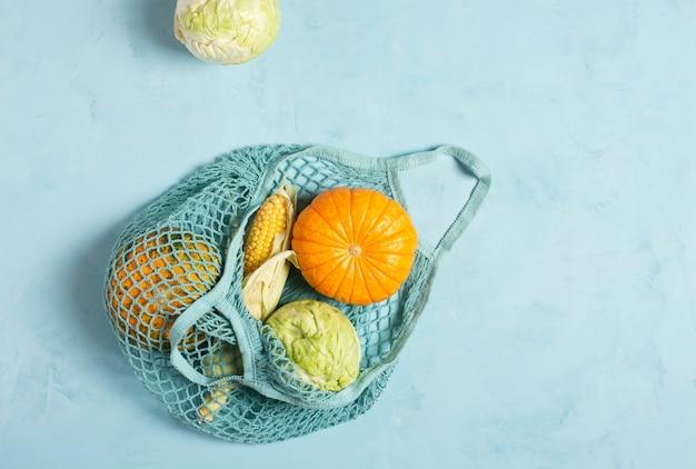 Verse groenten in een milieuvriendelijk gaas op een lichtblauwe ondergrond, zero waste concept.