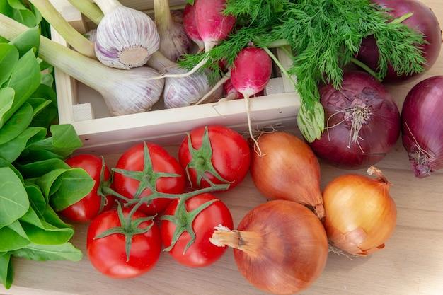 Verse groenten in houten doos op houten achtergrond. het concept van gezonde biologische voeding.