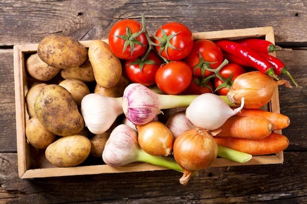 Verse groenten in houten kist op oude houten tafel, bovenaanzicht