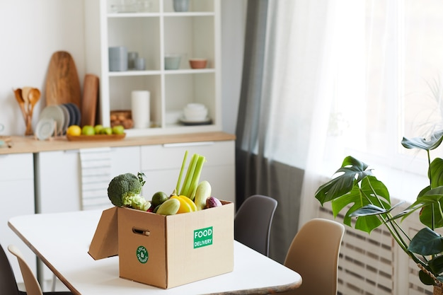 Verse groenten in kartonnen doos op tafel in binnenlandse keuken