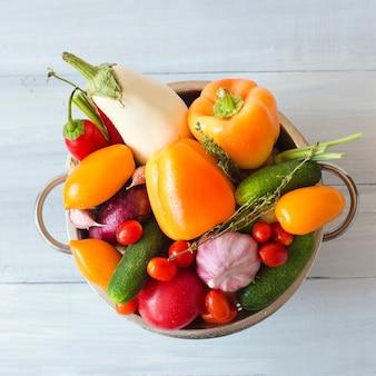 Verse groenten in metalen vergiet over wit. gezond eten bovenaanzicht.