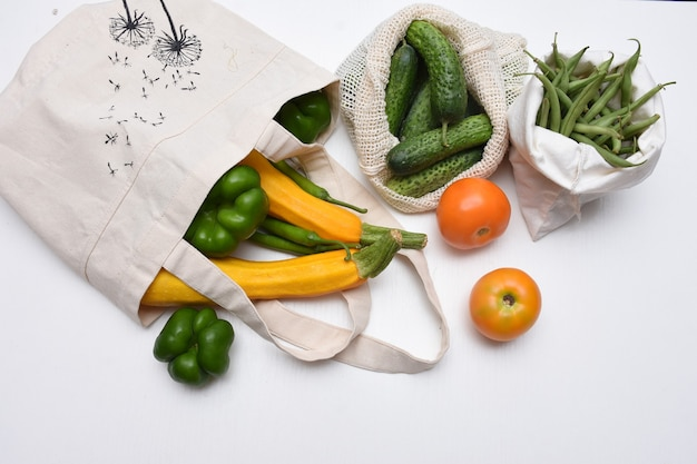 Verse groenten in witte eco-opbergzakken. tomaten, paprika's, courgette, komkommers, bonen. geen afvalconcept.
