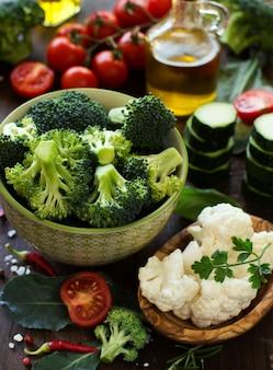 Verse groenten, kruiden en olijfolie op een houten tafel