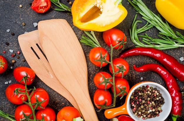 Verse groenten kruiden kruiden ingrediënten voor gezond koken of salade maken op donkere rustieke achtergrond met ruimte voor uw tekst. bovenaanzicht