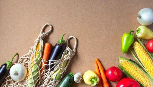 Verse groenten, mesh boodschappentas op ambachtelijke achtergrond. kopieer ruimte, plat lag.