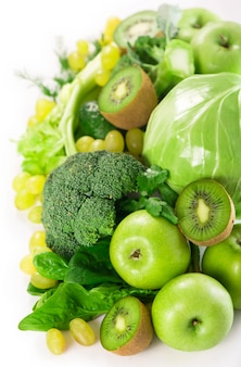 Verse groenten met bladeren - broccoli, kiwi, selderij, spinazie, boerenkool, druiven en appel geïsoleerd op een witte achtergrond