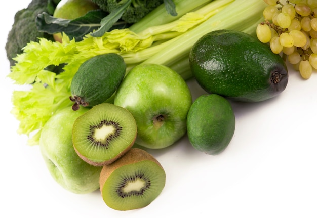 Verse groenten met bladeren - kiwi, druiven, appels en crashes, komkommers, courgette, broccoli, kool en groenen geïsoleerd op een witte ondergrond