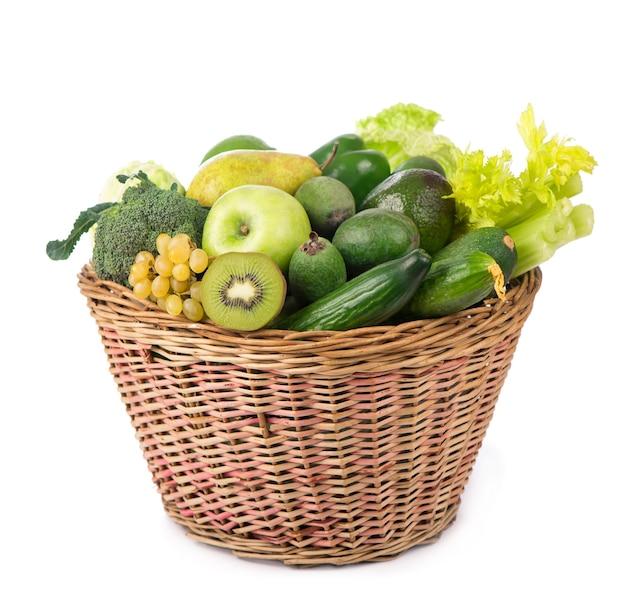 Verse groenten met bladeren - kiwi, druiven, appels en crashes, komkommers, courgette, broccoli, kool en groenen in de mand geïsoleerd op een witte ondergrond