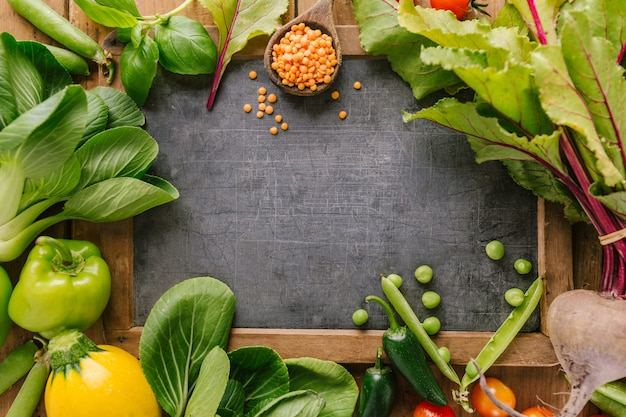 Verse groenten met bord op houten tafel