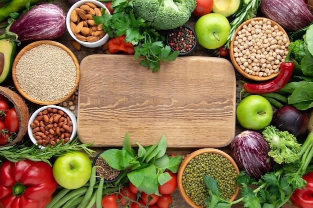 Verse groenten, ontbijtgranen: mungboon, kikkererwten, quinoa, noten, houten keukenplank voor uw tekst.